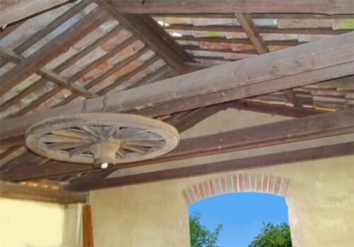 soffitto a capriata in legno con lampadario a ruota di carro impresa edile rec